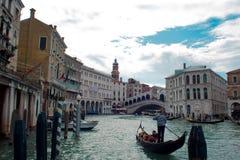 威尼斯,意大利- 2017年10月8日:平底船的船夫在大运河, Rialto桥梁在背景中漂浮 库存图片