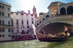 威尼斯,意大利- 2017年10月7日:平底船的船夫在大运河, Rialto桥梁在背景中漂浮 库存照片