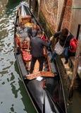 威尼斯,意大利- 2017年10月13日:平底船的船夫帮助在长平底船的乘客网络 长平底船富有地装饰 免版税图库摄影