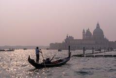 威尼斯,意大利- 2017年10月13日:平底船的船夫操作有游人的一艘长平底船在运河的水域中重创在 免版税图库摄影