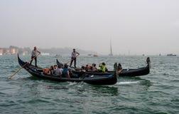 威尼斯,意大利- 2017年10月13日:平底船的船夫操作有游人的长平底船在重创的运河的水域中 游人 免版税库存照片
