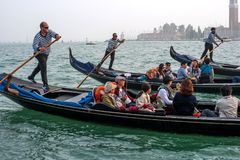 威尼斯,意大利- 2017年10月13日:平底船的船夫操作有游人的长平底船在重创的运河的水域中 游人 库存图片