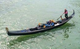 威尼斯,意大利- 2017年10月13日:平底船的船夫操作有游人的长平底船在重创的运河的水域中 游人 免版税库存图片