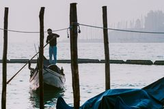 威尼斯,意大利- 2017年10月6日:平底船的船夫给与圣乔治di Maggiore教会的系泊缆背景的 免版税库存照片