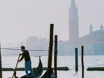 威尼斯,意大利- 2017年10月6日:平底船的船夫给与圣乔治di Maggiore教会的系泊缆背景的 免版税库存图片