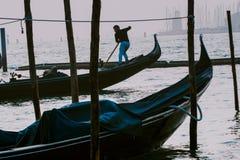 威尼斯,意大利- 2017年10月6日:平底船的船夫给与圣乔治di Maggiore教会的系泊缆背景的 图库摄影