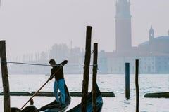 威尼斯,意大利- 2017年10月6日:平底船的船夫给与圣乔治di Maggiore教会的系泊缆背景的 库存照片