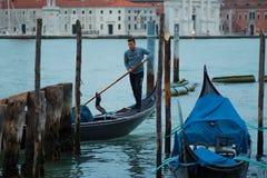 威尼斯,意大利- 2017年10月8日:平底船的船夫给与圣乔治di Maggiore教会的系泊缆背景的 库存照片