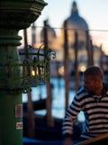 威尼斯,意大利- 2017年10月7日:平底船的船夫给与圣乔治di Maggiore教会的系泊缆背景的 图库摄影
