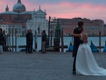 威尼斯,意大利- 2017年10月8日:拥抱在圣马可广场的新娘和新郎,在背景的长平底船 库存图片
