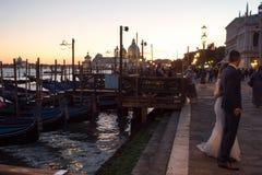 威尼斯,意大利- 2017年10月7日:新娘和新郎在圣马可广场,长平底船在背景 免版税库存图片