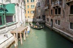 威尼斯,意大利- 2012年3月11日:有平底船的船夫划船的典型的长平底船沿一条狭窄的运河在威尼斯 免版税库存照片