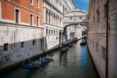威尼斯,意大利- 2017年6月10日:有游人的长平底船通过往叹气Ponte dei著名桥梁的小运河的  库存图片