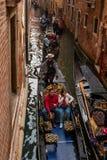 威尼斯,意大利- 2017年10月13日:游人在一条狭窄的运河的一艘长平底船航行 长平底船用红色富有地装饰 库存照片
