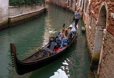 威尼斯,意大利- 2017年10月13日:游人在一条狭窄的运河的一艘长平底船航行 长平底船用红色富有地装饰 图库摄影