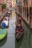 威尼斯,意大利- 2017年10月13日:游人在一条狭窄的运河的一艘长平底船航行 长平底船用红色富有地装饰 库存图片