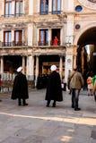 威尼斯,意大利- 2012年3月11日:红色礼服身分的妇女在古老大厦阳台在威尼斯 免版税库存照片