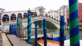 威尼斯,意大利- 2017年2月23日:运河重创与杆对停泊绿色和蓝色和在的Rialto桥梁全景  图库摄影