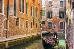 威尼斯,意大利- 2018年8月22日:长平底船由威尼斯一条狭窄的街道运河的一名平底船的船夫统治了  免版税库存图片