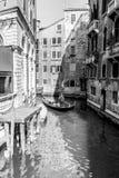 威尼斯,意大利- 2012年3月11日:有平底船的船夫划船的典型的长平底船沿一条狭窄的运河在威尼斯,黑白图象 图库摄影