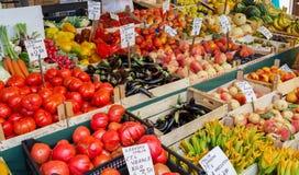 威尼斯,意大利- 2016年9月:Rialto鱼市 鱼贩子在工作 有蕃茄,桃子,花,夏南瓜的价格的片剂 免版税库存图片