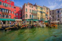 威尼斯,意大利- 2015年6月18日:各种各样的长平底船和小船在口岸在威尼斯街道,商业街 餐馆 库存图片