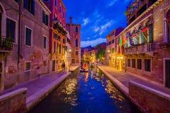 威尼斯,意大利- 2015年6月18日:天空在威尼斯在夏天 在走动运河的人和轻使用的小船航行 库存图片
