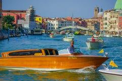 威尼斯,意大利- 2015年6月18日:未认出的小船司机,威尼斯出租汽车 在水中间的木小船 免版税库存照片