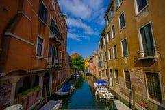 威尼斯,意大利- 2015年6月18日:著名威尼斯运河,停车处小船浪漫照片在房子中间的 免版税库存图片