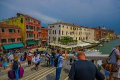 威尼斯,意大利- 2015年6月18日:visitting在威尼斯入口的游人一座灰色桥梁  运河和水 免版税库存图片
