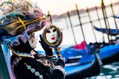 威尼斯, 2月10日:在传统威尼斯狂欢节期间,典型的礼服的一名未认出的妇女调查镜子 免版税库存照片