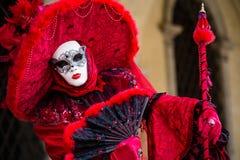 威尼斯, 2月10日:在传统威尼斯狂欢节期间,典型的红色礼服的一名未认出的妇女摆在 免版税库存图片