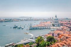 威尼斯-大运河全景有长平底船、大教堂圣玛丽亚della致敬和房子,威尼斯, Ita红色铺磁砖的屋顶的  免版税库存照片