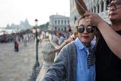 威尼斯- 10月04 :未知的亚裔游人在10月04日做在著名Ponte dei Sospiri桥梁前面的一selfie 免版税库存照片