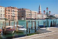 威尼斯-重创的运河和小船和钟楼 库存图片