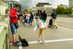威斯敏斯特桥梁的伦敦风笛球员 库存图片