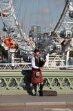 威斯敏斯特桥梁的风笛球员 图库摄影