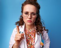 威胁与在蓝色的手指的Paediatrist医生 免版税库存照片