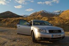 威廉堡,苏格兰- 2013年3月:一辆灰色奥迪汽车的看法在风景苏格兰山前面的 库存图片