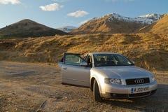 威廉堡,苏格兰- 2013年3月:一辆灰色奥迪汽车的看法在风景苏格兰山前面的 库存照片