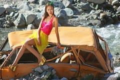 娃娃窗框的妇女坐一辆残破的汽车在阳光下有玩具熊的在手中 免版税库存照片
