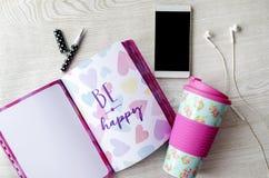 娘儿们热水瓶、笔记本、电话和耳机在白色木桌上 免版税图库摄影