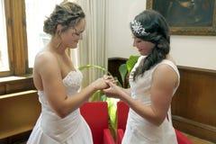 结婚交换圆环的两个新娘 免版税库存图片