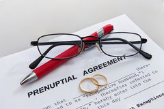婚前约定形式和两个婚戒 免版税库存图片
