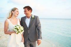 结婚在海滩仪式的新娘和新郎 免版税库存照片