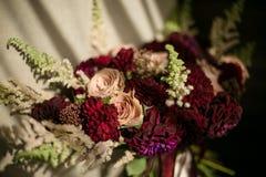 婚姻与深紫红色大丽花的被弄乱的花束,提取乳脂玫瑰和绿色 接近的照片 库存照片