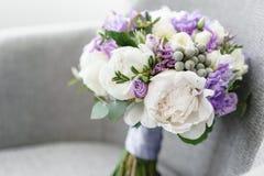 婚姻与牡丹、小苍兰和其他花的新娘花束在黑胳膊椅子 轻和淡紫色春天颜色 早晨 免版税库存照片
