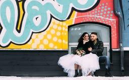 婚姻仿照岩石样式 摇摆物或骑自行车的人婚礼 有时髦的皮夹克的人 它` s rocknroll婴孩 甜点 库存照片