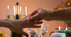 婚姻提议  人在女孩手指上把圆环放 瓶与二块玻璃的香槟 夜间人浪漫日落等待的妇女 股票录像