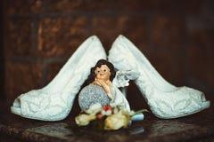 婚姻新娘鞋子的典雅的白色鞋带高跟与在黑褐色背景,新娘的早晨的一个小雕象 免版税库存图片